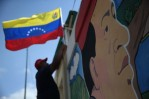 A worker hags a flag outside a military barracks where Hugo Chavez is entombed on March 4, 2014 in Caracas, Venezuela.