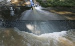 A drainage pipe pumps water out of a basement June 29, 2006 outside of Wilkes-Barre, Pennsylvania