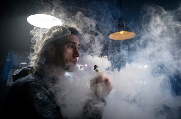 A smoker exhales the vapor from the e-cigarette product at a vaping shop in Bristol, England.