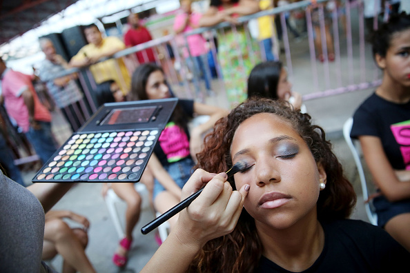 A model is prepared with makeup at a fashion show thrown by 'Jacare e Moda' in the Jacarezinho community, or 'favela', on November 1, 2014 in Rio de Janeiro, Brazil